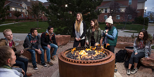 group of students gathered around firepit
